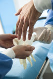 Surgeon wearing protective gloves Stock Images