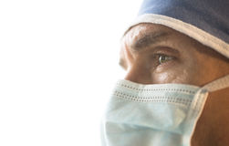 Surgeon Wearing Surgical Mask And Cap Looking Away. Side view of male surgeon wearing surgical mask and cap looking away against white background Royalty Free Stock Image
