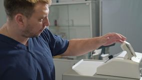 The surgeon in a white sterile dressing gown works in a hospital with medical equipment. A doctor in a clinical. Laboratory performs a blood test stock footage