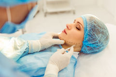 Surgeon at work. Surgeon is performing a plastic surgery using a scalpel, in a modern operating room, close up Stock Photos