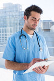 Surgeon writing in clipboard. In clinic Royalty Free Stock Photos