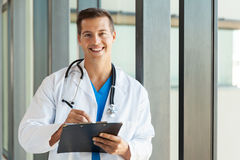Surgeon writing clipboard. Portrait of young surgeon writing on clipboard in hospital Royalty Free Stock Images