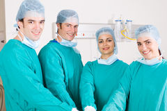 Surgeons. A team of surgeons in surgical gowns and maskss putting their hands together Stock Photography