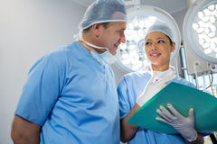 Surgeons discussing over file. In operation theater Royalty Free Stock Photo