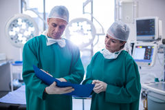 Surgeons discussing over medical reports in operation room royalty free stock photography