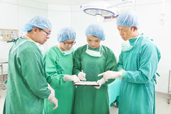 Surgeons discussing patient records in operation room Royalty Free Stock Photos