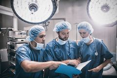 Surgeons discussing patient records in operation room. At hospital royalty free stock photo