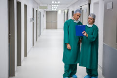 Surgeons discussing report on clipboard in corridor Royalty Free Stock Images
