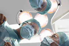 Surgeons Discussing Surgery In Operating Theatre Royalty Free Stock Photos