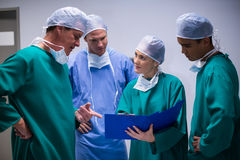 Surgeons having discussion on file in corridor Royalty Free Stock Images