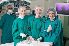 Surgeons. With instruments looking at camera with colleagues performing in background Royalty Free Stock Photos