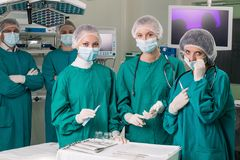Surgeons. With instruments looking at camera with colleagues performing in background Royalty Free Stock Photo