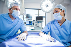 Surgeons interacting with each other. In operation theater Royalty Free Stock Image