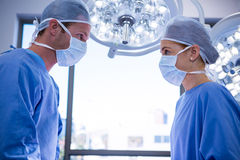 Surgeons interacting with each other in operation theater. At hospital Stock Photography
