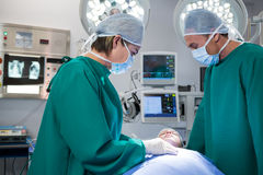 Surgeons interacting while operating patient Royalty Free Stock Photography