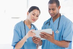 Surgeons looking at digital tablet in hospital Royalty Free Stock Image