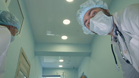 Surgeons looking down at patient getting ready for urgent surgery. Close up shot. Professional shot in 4K resolution. 098. You can use it e.g. in your royalty free stock images
