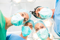 Surgeons operating patient in operation theater. Hospital - surgery medical team of doctors in operation room or Op operating on patient in an emergency Stock Photos