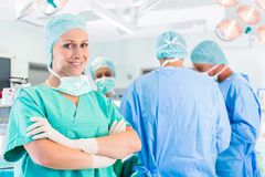 Surgeons operating patient in operation theater. Hospital - surgery team in the operating room or Op of a clinic operating on a patient in emergency Stock Photos