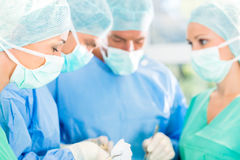 Surgeons operating patient in operation theater. Hospital - surgery team in the operating room or Op of a clinic operating on a patient, perhaps it`s an Stock Images