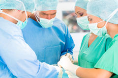 Surgeons operating patient in operation theater. Hospital - surgery team in the operating room or Op of a clinic operating on a patient, perhaps it`s an Stock Image