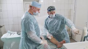 Surgeons in the operating room make the uzi of the patient`s legs. Discuss the course of surgery to remove veins. The. Surgical department of the hospital stock video footage