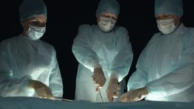 Surgeons perform an operation or procedure. Doctor with grasper or forcep and tweezer. Assistants help during surgery In. Doctor with grasper or forcep and stock footage