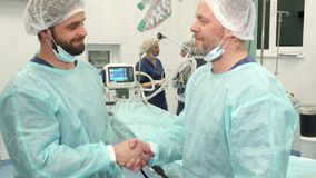 Surgeons shake their hands. Two surgeons shaking their hands at the surgery room. Mature doctor and his younger colleague standing against background of medical Royalty Free Stock Images