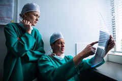 Surgeons sitting at window and checking x-ray Royalty Free Stock Photography