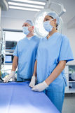 Surgeons standing in operation theater. Surgeons wearing surgical mask and standing in operation theater Stock Image