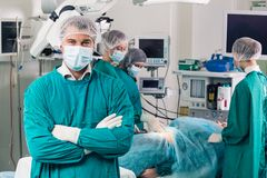 Surgeons. Surgeon looking at camera with colleagues Stock Photo
