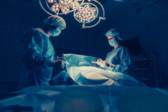 Surgeons team working with Monitoring of patient in surgical operating room. breast augmentation Royalty Free Stock Photography