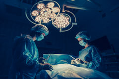 Surgeons team working with Monitoring of patient in surgical operating room. breast augmentation Stock Photos