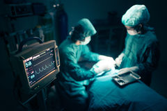 Surgeons team working with Monitoring of patient in surgical operating room. Royalty Free Stock Photos