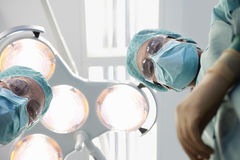 Surgeons Under Surgery Lights In Operating Theatre Royalty Free Stock Photo