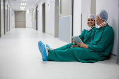 Surgeons using digital tablet in corridor. Of hospital Stock Photography