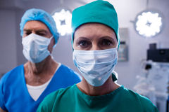 Surgeons wearing surgical mask in operation theater. Of hospital Royalty Free Stock Photography