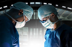 Surgery. Doctors team in surgery in a dark background Royalty Free Stock Images