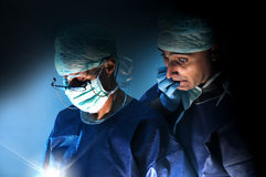 Surgery. Doctors team in surgery in a dark background Royalty Free Stock Photo