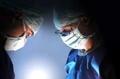 Surgery. Doctors team in surgery in a dark background Stock Photos