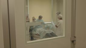 Surgery of eye behind the door of operation room stock footage