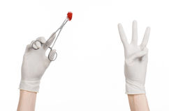 Surgery and Medical theme: doctor's hand in a white glove holding a surgical clip with a bloody tampon isolated Royalty Free Stock Photo