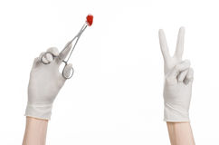 Surgery and Medical theme: doctor's hand in a white glove holding a surgical clip with a bloody tampon isolated Stock Images