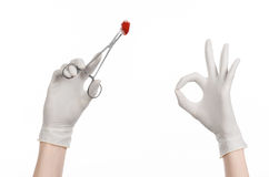 Surgery and Medical theme: doctor's hand in a white glove holding a surgical clip with a bloody tampon isolated Royalty Free Stock Photos