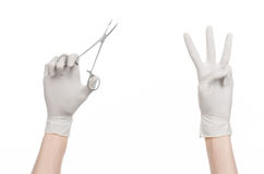 Surgery and Medical theme: doctor's hand in a white glove holding a surgical clip isolated on white background Stock Photography