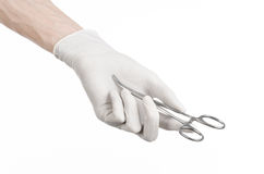 Surgery and Medical theme: doctor's hand in a white glove holding a surgical clip isolated on white background Royalty Free Stock Image