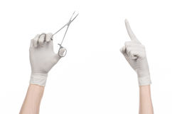 Surgery and Medical theme: doctor's hand in a white glove holding a surgical clip isolated on white background Royalty Free Stock Images