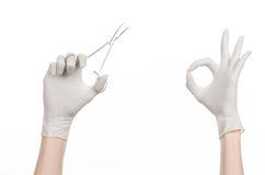 Surgery and Medical theme: doctor's hand in a white glove holding a surgical clip isolated on white background Royalty Free Stock Photo