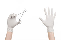 Surgery and Medical theme: doctor's hand in a white glove holding a surgical clip isolated on white background Stock Photo