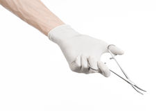Surgery and Medical theme: doctor's hand in a white glove holding a surgical clip isolated on white background Stock Image